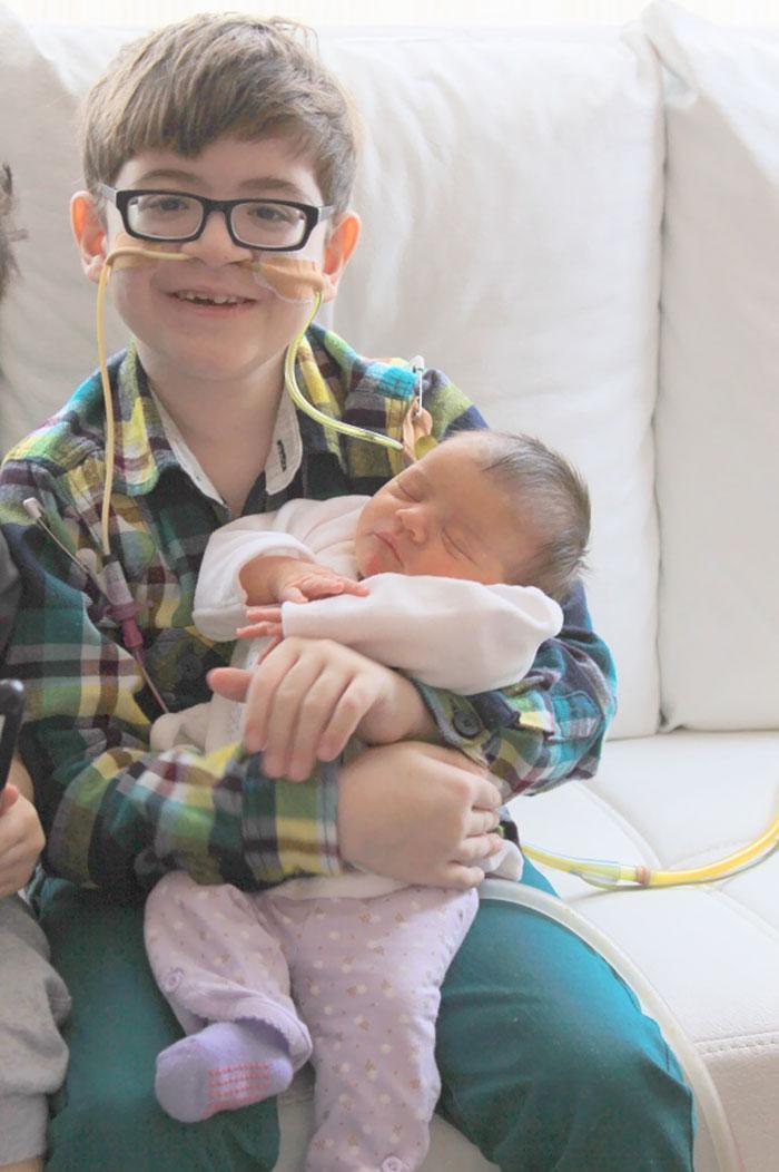 Criança segurando sua irmã recém nascida no colo