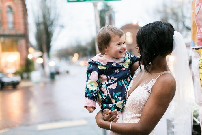 A noiva segurando a garotinha de 2 anos no colo