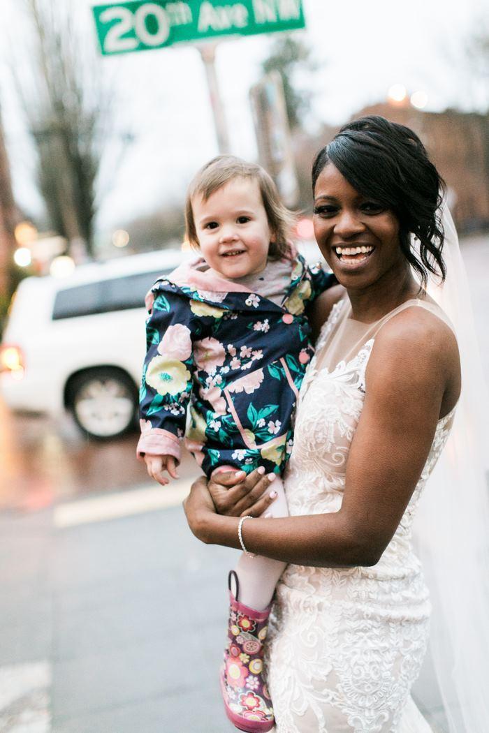 A noiva sorrindo com a garotinha no colo