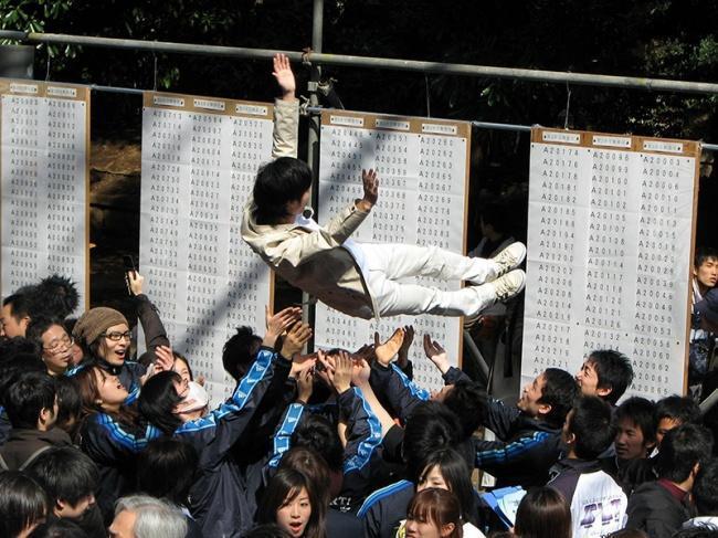 Aluno japonês sendo jogado para o alto pelos colegas por ter sido aprovado na universidade