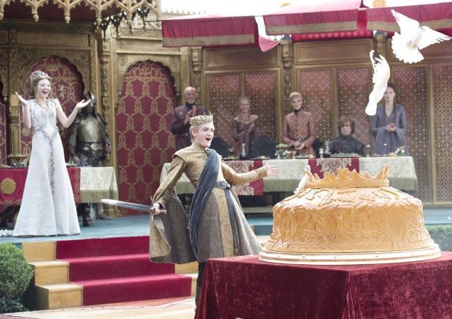 Rei Joffrey comemorando ao ver as pombas saindo do bolo