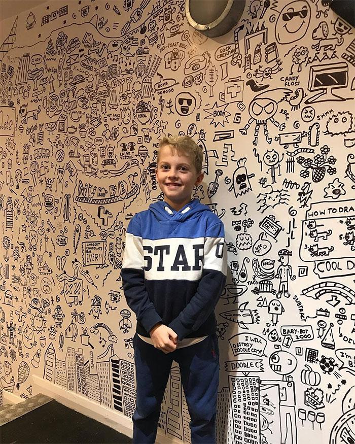 Imagem mostra o garotinho orgulhoso de ter finalizado seu trabalho decorando as paredes do restaurante com seus desenhos