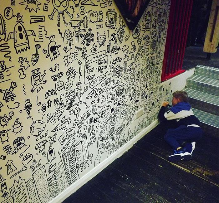 Garotinho deitado no chão desenhando próximo ao rodapé para deixar a parede inteiramente decorada