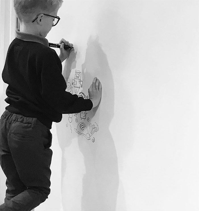 Foto mostra o garotinho iniciando os desenhos em uma nova parede