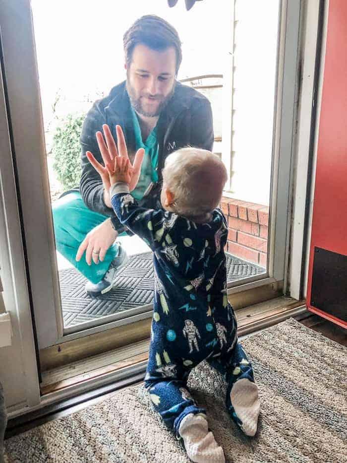 Fotografia de médico isolado sem poder tocar no filho reflete a dor da pandemia